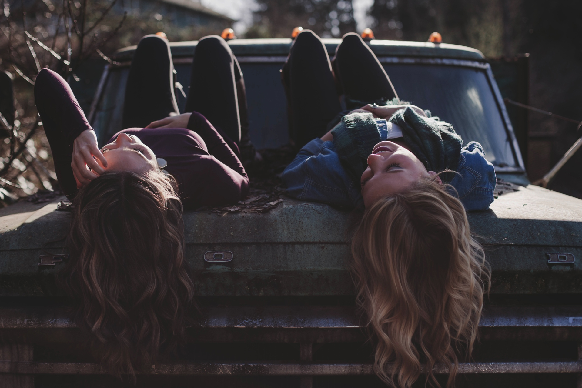 two friends lying on car bonnet